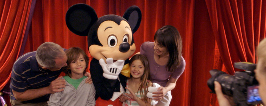 Mickey Mouse posing with a family, having a photo taken by a Disney PhotoPass photographer