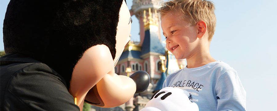 Little boy meets Mickey Mouse