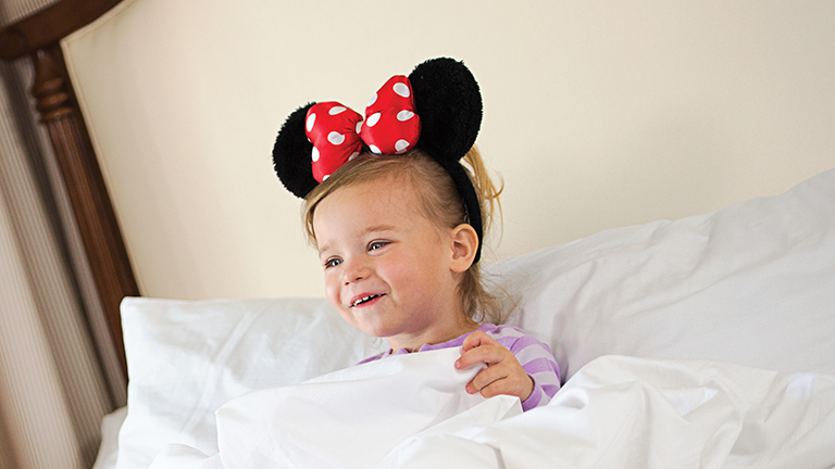 Young guest in bed, wearing Minnie ears