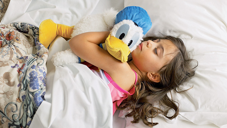 Young guest hugging Donald Duck plush