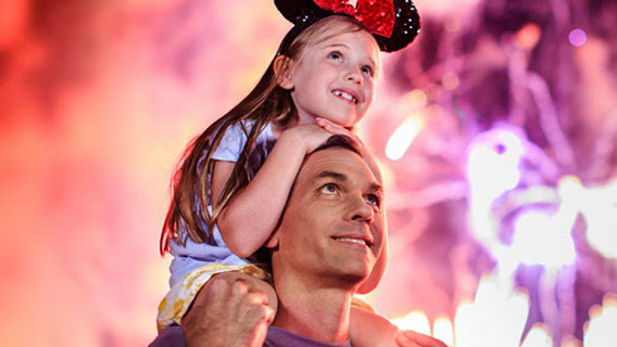 Young guest watching the fireworks display at Magic Kingdom with her father