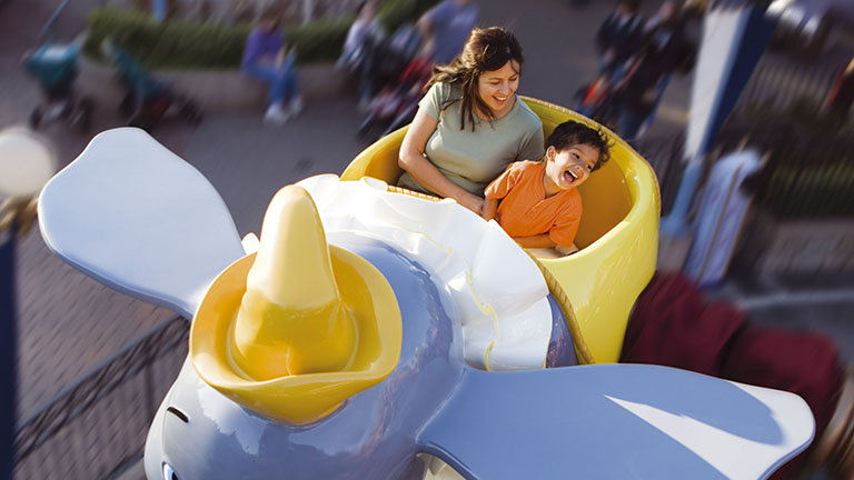 Mother and son having fun on Dumbo the Flying Elephant in Fantasyland