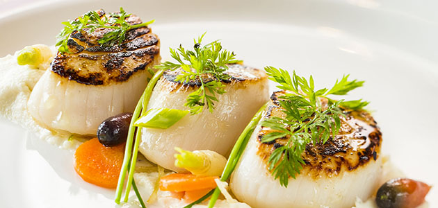 Seared sea scallops served at the adult-exclusive restaurant Palo.