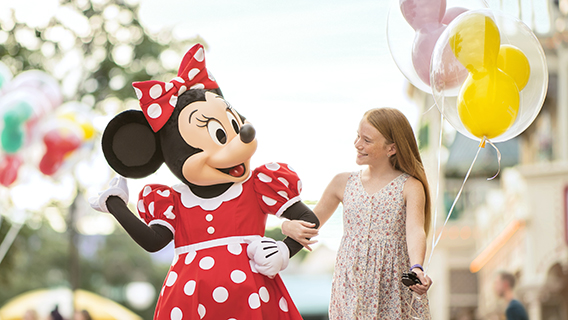 Young guest walking with Minnie Mouse