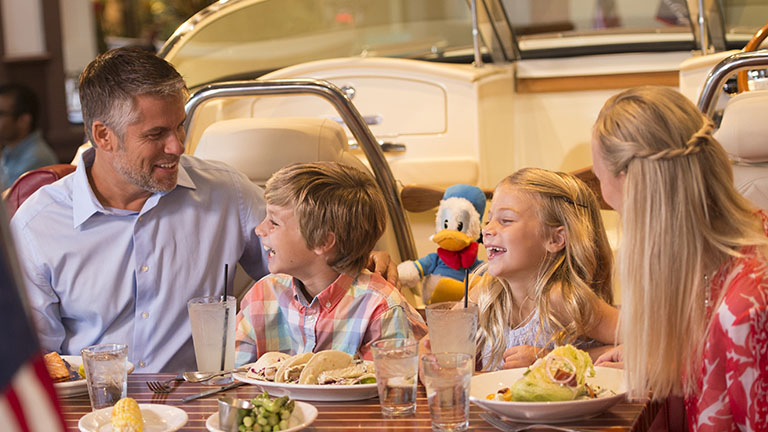 Family having dinner in an amphicar at The Boathouse, Disney Springs