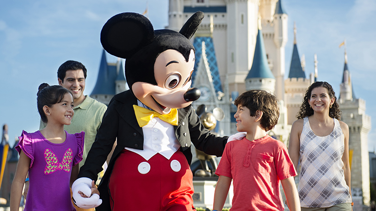 Mickey Mouse walking with a family at Magic Kingdom