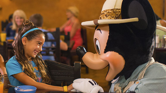 Family enjoying a character breakfast, joined by Mickey Mouse at Tusker House