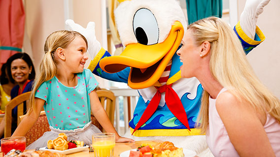 Family enjoying a Character Dining experience joined by Donald Duck