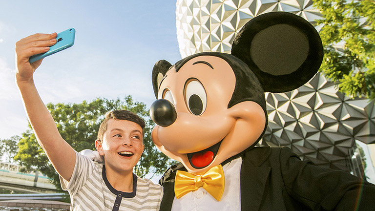 Young guest snaps a selfie with Mickey Mouse in Epcot